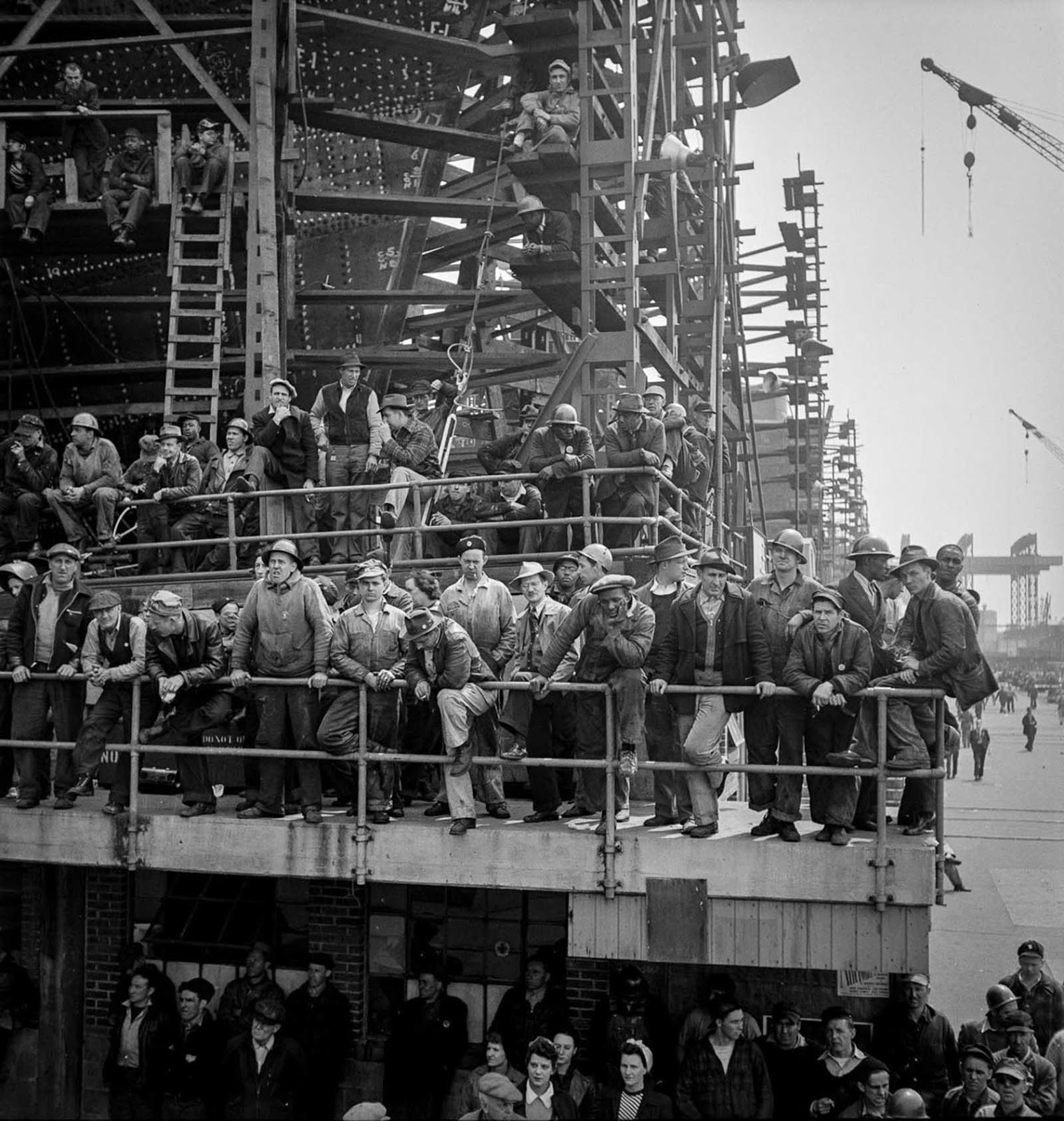"Workers gather to watch a launching ceremony. The Bethlehem-Fairfield Shipyard on Baltimore Harbor was established in February and quickly set 27,000 employees to work building these new ""Liberty ships""."