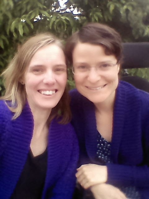 Jodie and her friend both wearing purple cardigans with ribbed collars and cuffs.  Jodie's cardigan is the hand crocheted Belcarra cardigan which has a lace stitch pattern. Her friend is wearing a shop-bought knitted cardigan, the body of which is a solid knit stitch.
