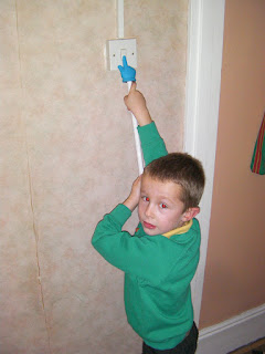 using a rubber hand on a stick to operate a light switch