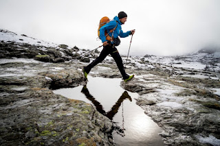 Hiker crossing mountain stream, Norway