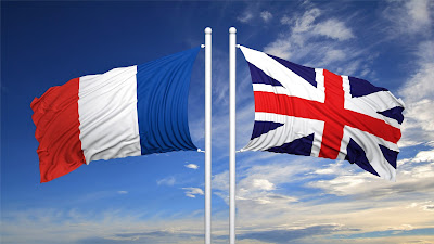 Pic of French and British flags flying at top of flagpoles in opposite directions