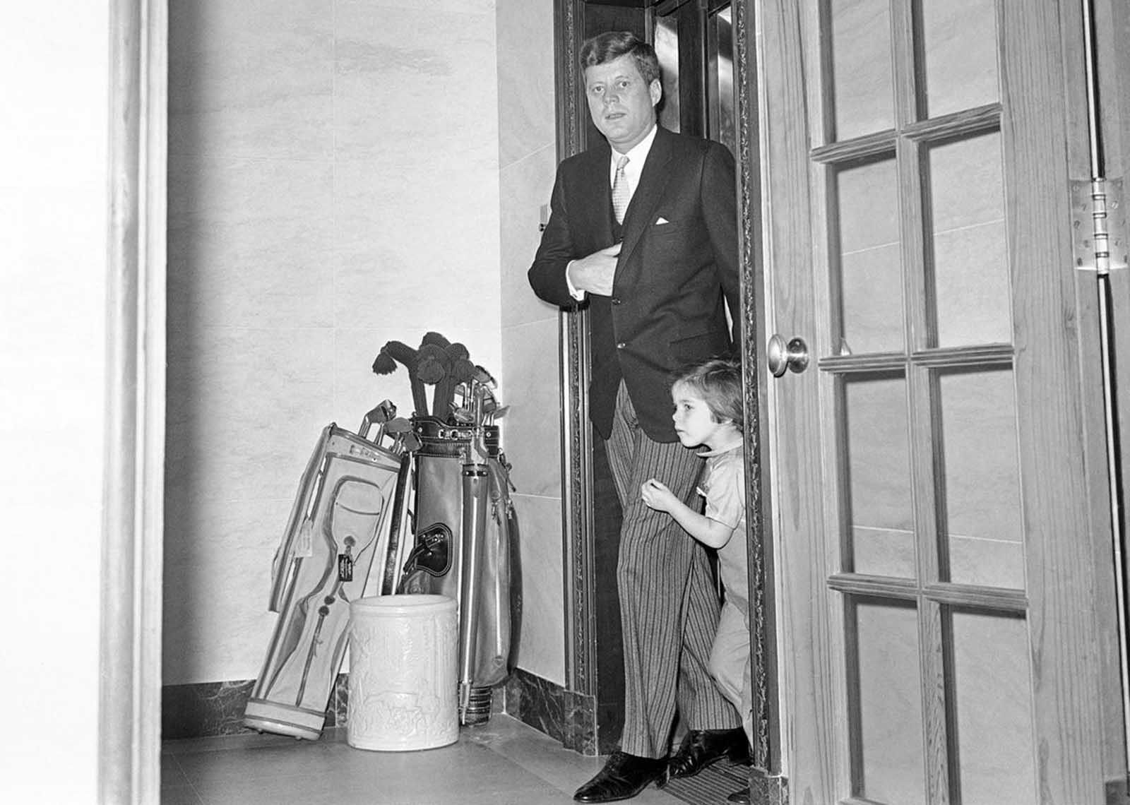 Three-year-old Caroline Kennedy pushes past her father as he leaves the elevator at the White House ground floor, on March 16, 1961, to begin a typical busy day at 9:42 A.M. President Kennedy has a strip of tape across a cut above his left eye, suffered when his head struck a table as he was bending over to pick up something for Caroline.