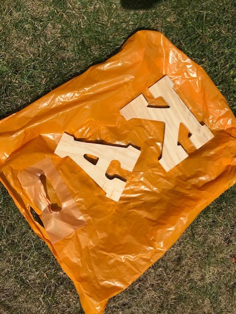 Plastic bag laid out on grass with the wooden letters laid on their front