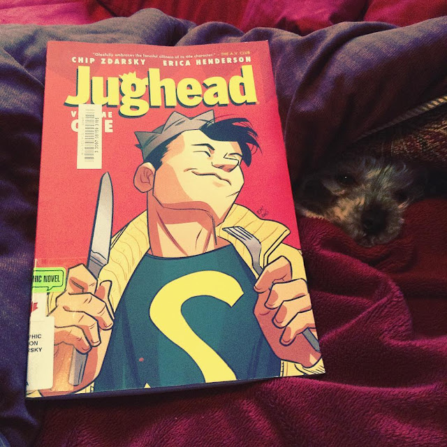 Murchie peeks his head out of a blanket cave. Propped up on the blankets beside him is a trade paperback copy of Jughead Volume One. Its red cover features a white boy wearing a grey crown hat, a blue t-shirt, and a yellow sweater. He smirks as he clutches a knife and fork.
