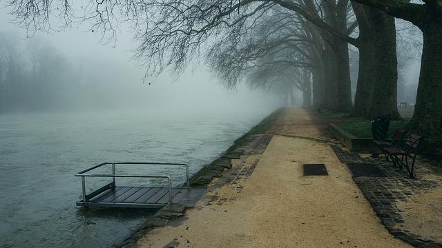 photo d'un ponton avec le fleuve en crue sous la brume