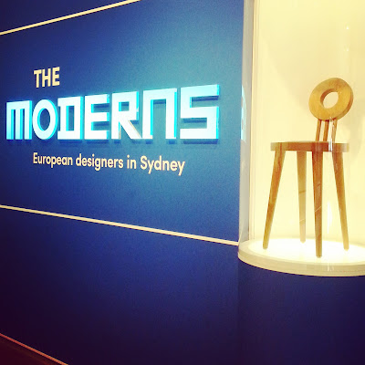Entry to The Moderns exhibition, with a modernist chair in a display cabinet.