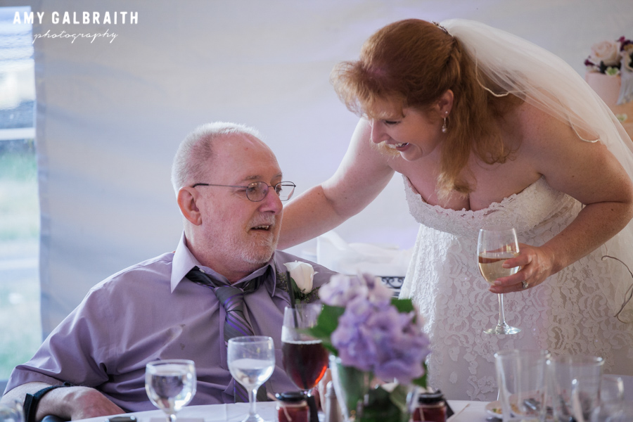 bride laughing with father at wedding reception