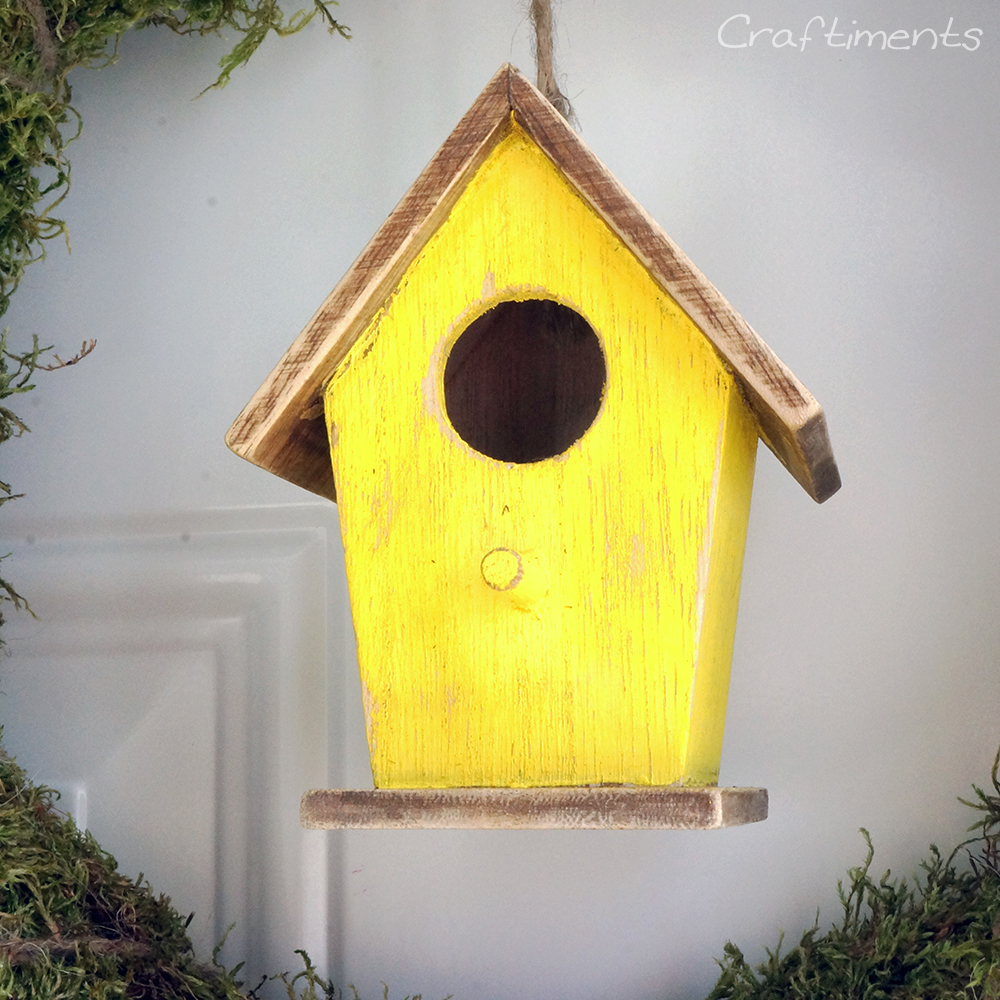Freesia yellow, distressed birdhouse hanging from a moss wreath