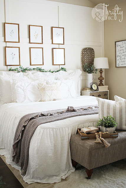 farmhouse bedroom with white ruffle bedding and gallery wall