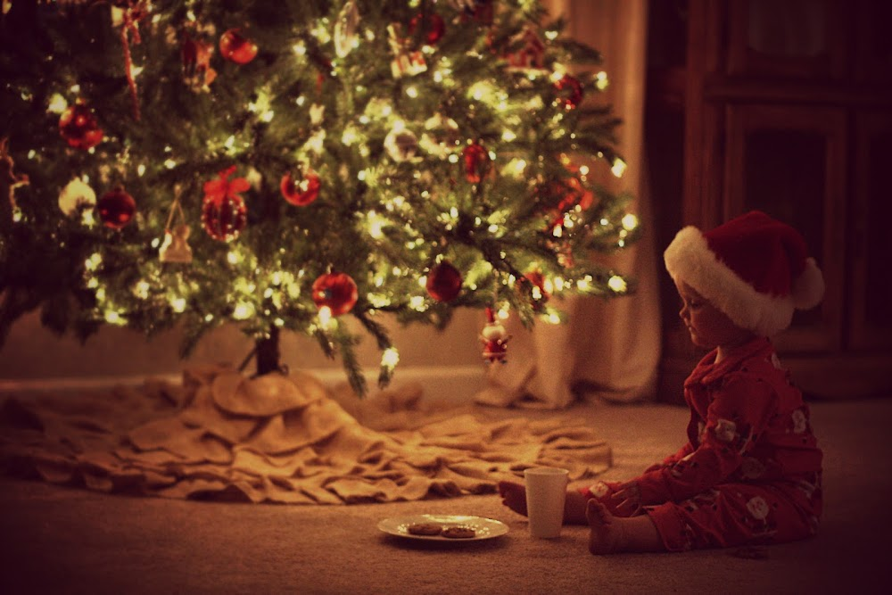 toddler sitting next to christmas tree