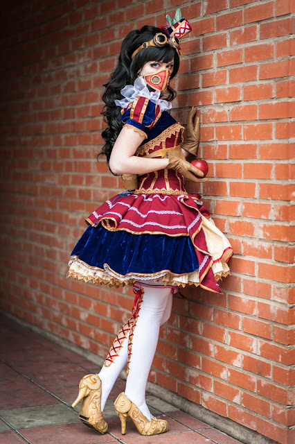 This Disney Steampunk cosplay is a take on Snow White. The girl is wearing a dress, mask, goggles, lace up stockings and high heels.