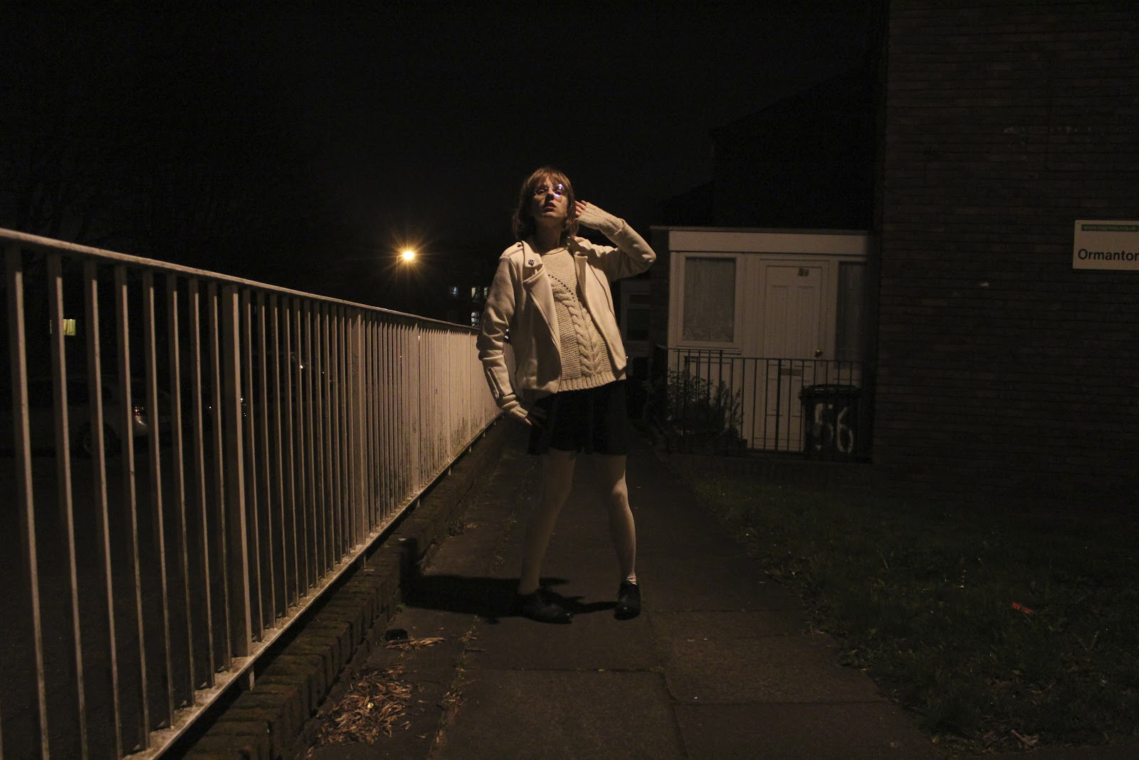 A woman strikes a pose on a pathway behind some houses. She looks like a child playing at being an adult.