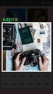 на столе лежат фотоаппараты и карта с письмами из разных мест