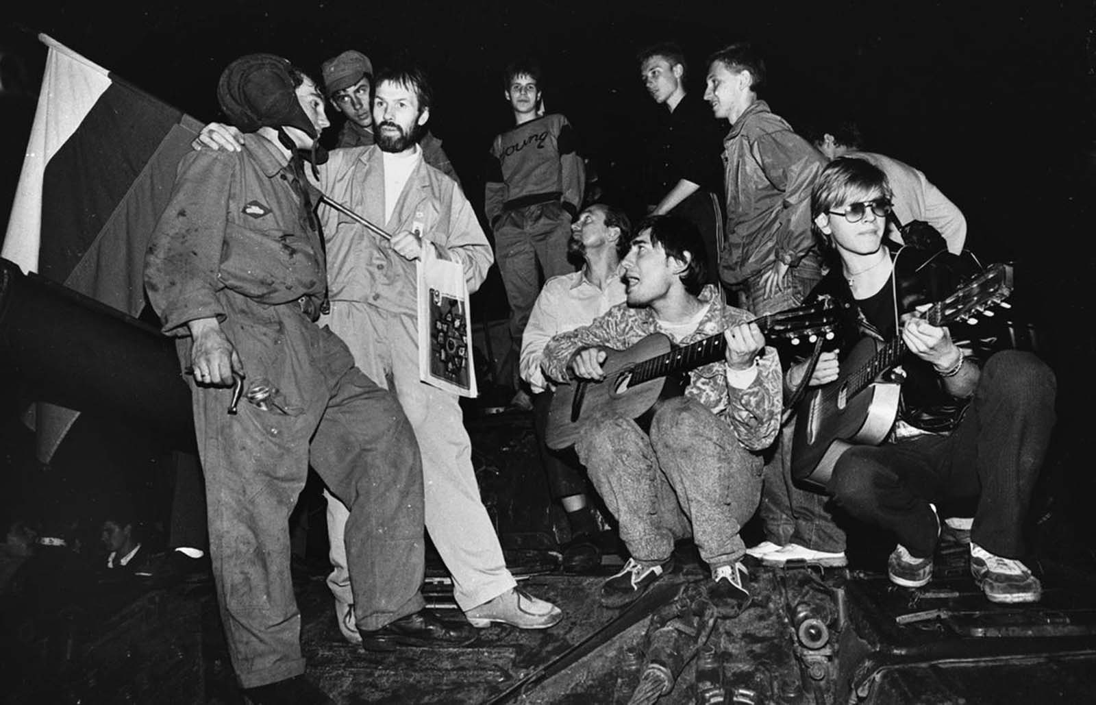 Residents play music and talk to soldiers in front of the Russian White House in central Moscow early on August 20, 1991.