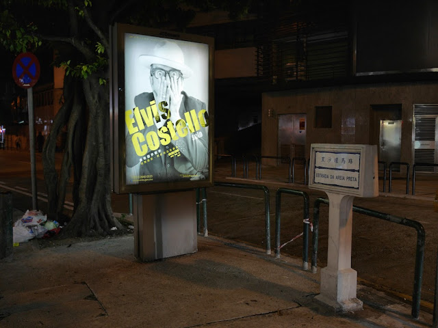 Advertisement sign for Elvis Costello concert next to a street sign for Estrada Da Areia Preta in Macau