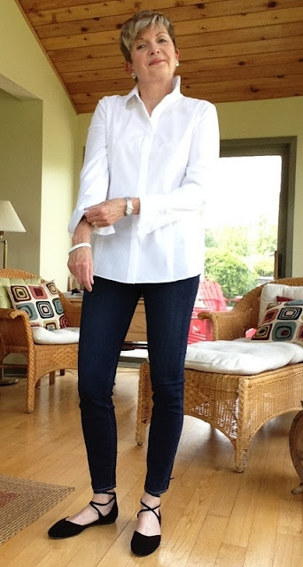 woman in white shirt, jeans, black flats, rolling up shirt sleeves