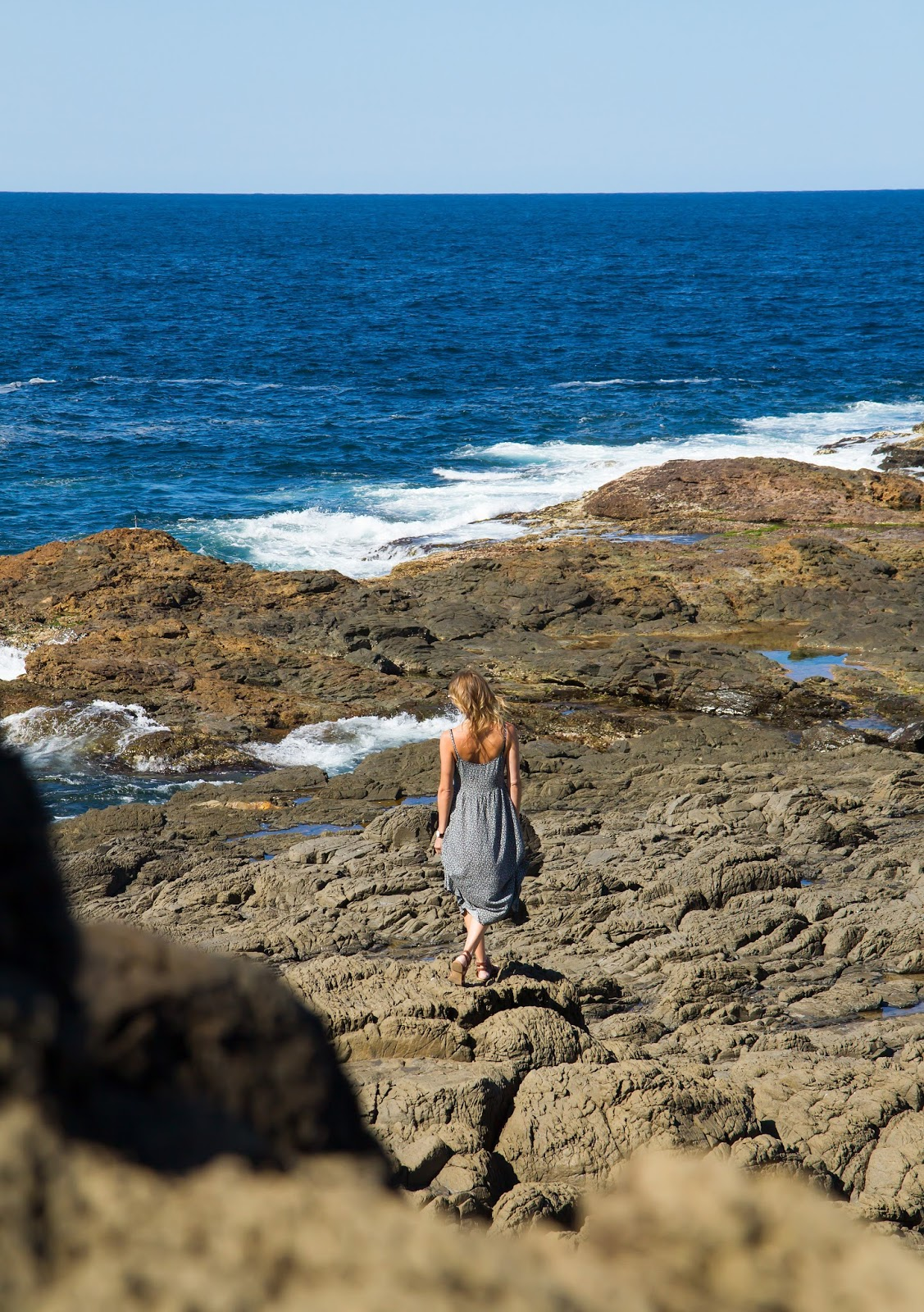 Travel blogger and digital nomad, Alison Hutchinson from Styling My Life, is walking along the rocks at the Kiama Blow Hole.