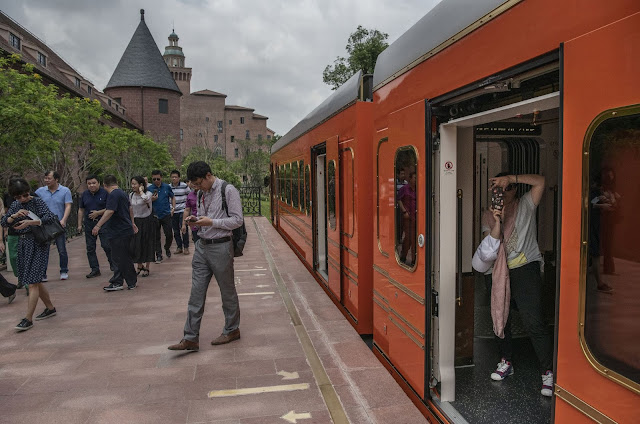 A woman takes a picture with her smartphone as others disembark from a train.