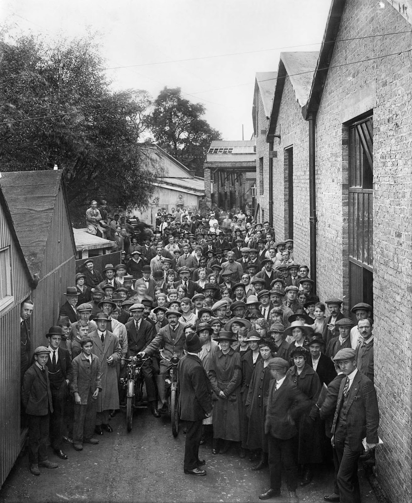 Belgian refugees outside the Belgian Munition Works in London, where they were employed to manufacture explosives for the war effort. 1918.