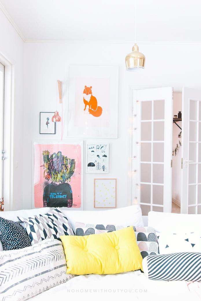detalle del sofá con cojines de colores, puerta blanca, cuadros de colores