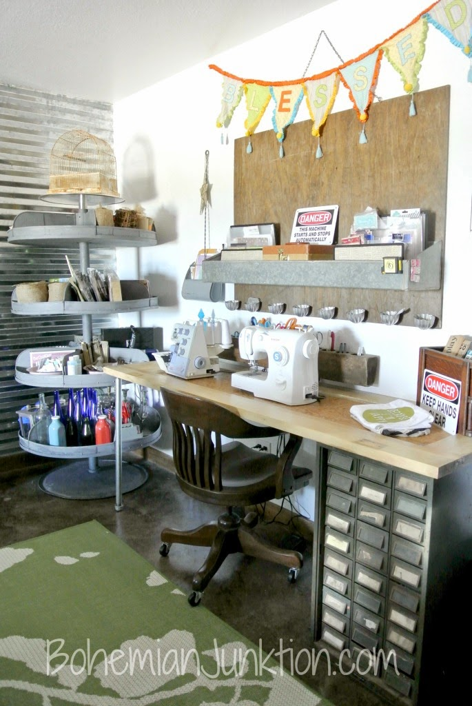 A small desk with a sewing machine on top. Beside it is a metal shelf with supplies.