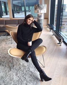 Девушка в черном свитере и джинсах в красивом кресле