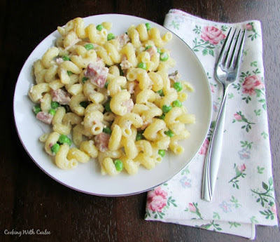pate full of pasta with ham peas and cream with a fork and flowery napkin
