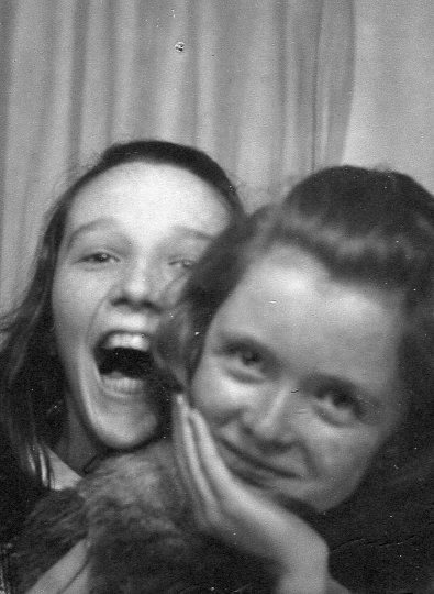 two girls laughing in a photo booth