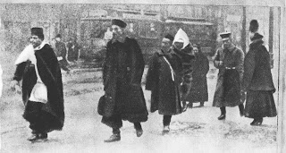 Black and white photo of seven African men walking down a street. They are all wearing turbans and wearing a thick black winter fur coat. Behind them passes by a tram.