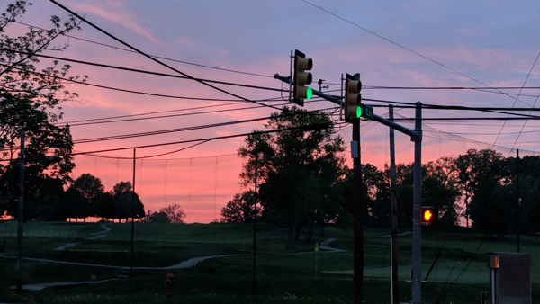 image of a very pink sky at sunset, over an intersection beside a golf course