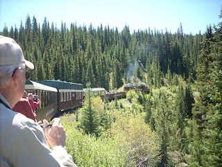 Outdoor photo of a train ride in the mountains on a sunny day with guests taking photos of the scenery.