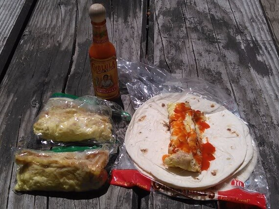 Omelettes cooked in Ziploc, one on a tortilla with Cholula hot sauce