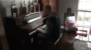 Man plays piano in Harvey-flooded home