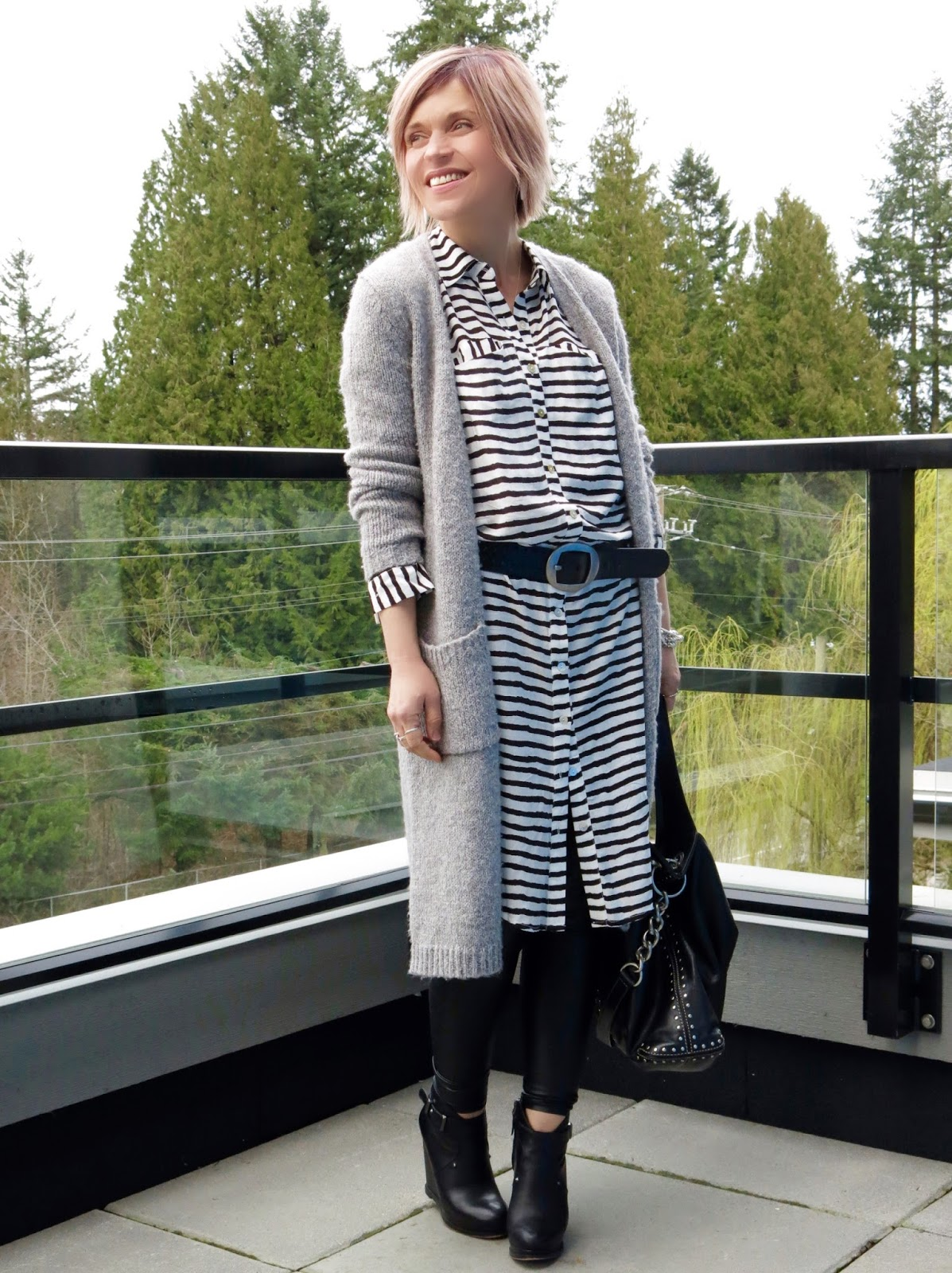 styling a striped shirtdress with faux-leather leggings, wedge booties, a belt, and long cardigan