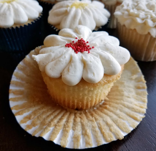 close up of white cupcake with wrapper pulled down