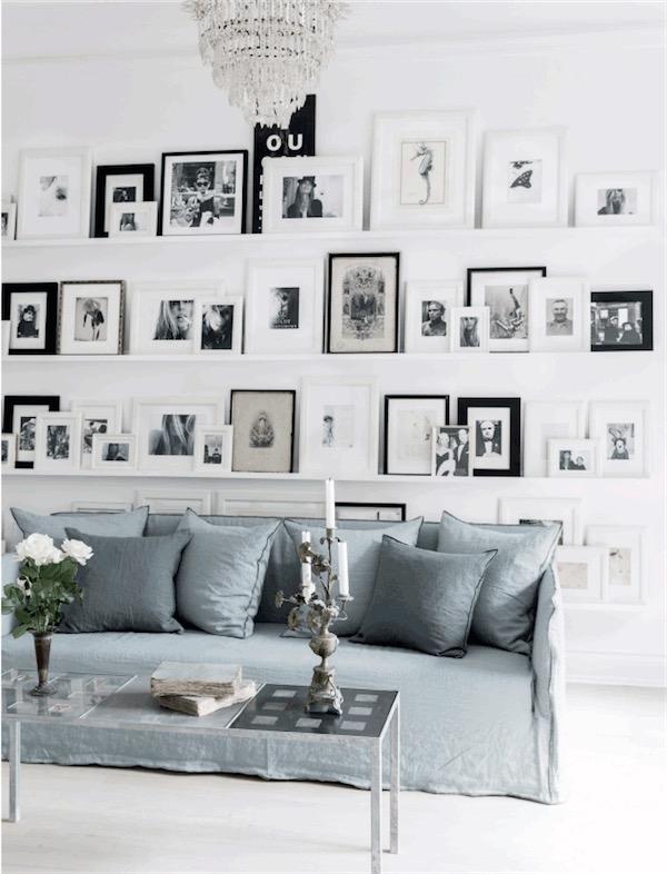 salon decorado con infinidad de marcos con imagenes y sofa gris azulado chicanddeco