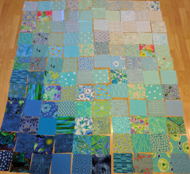 Blue fabric squares shading from white to navy make Double Vision quilt background.