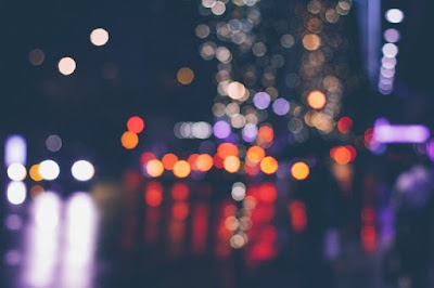 Imagen difuminada de una calle de noche donde únicamente se pueden apreciar las diferentes luces.