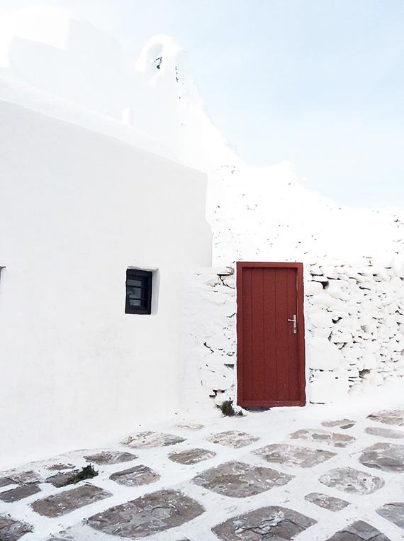 Red door on white wall in Mykonos. Greek minimalism. Photo by Eleni Psyllaki @myparadissi