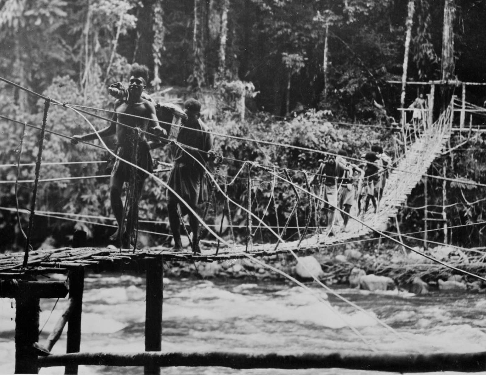 Men carry supplies over a newly built bridge.