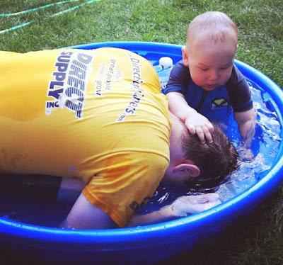 Papá jugando en una tina con su hijo