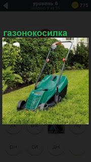 На газоне стоит газонокосилка, готовая косить траву и ждет применения