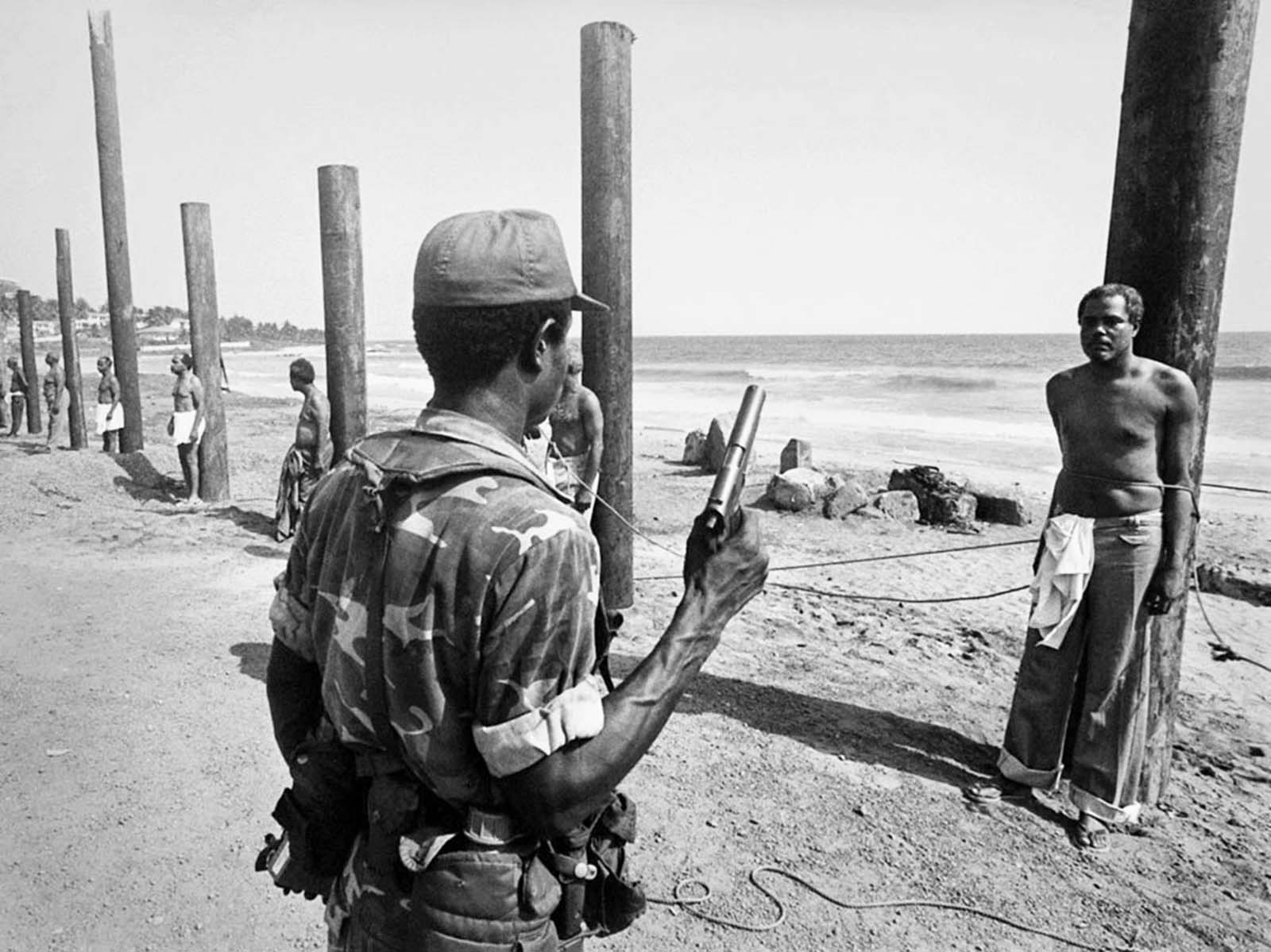 A Liberian army soldier stands ready to execute a former cabinet minister following the 1980 coup. The minister in the photo: Cecil Dennis.