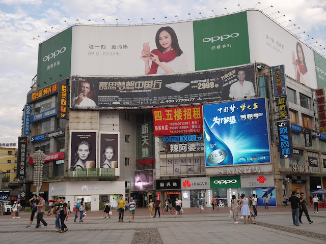Mengzhilan M6, Oppo, and Huawei advertisements displayed at Huaxing Square in Changsha