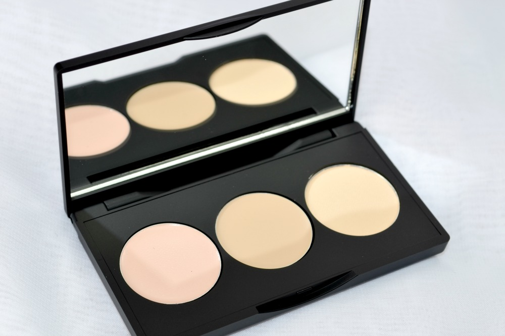 Image of the open palette with concealers and powder pan