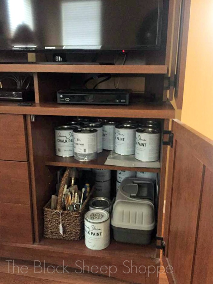 TV armoire used for paint storage