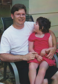 caregiver holding child with disabilities: Author and artist David Borden with his daughter, Savannah