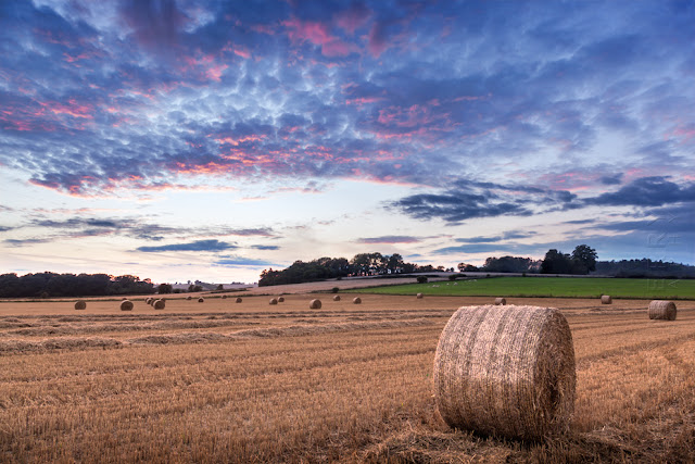 Colourful sunset colour above a Cotswold field of hay bales by Martyn Ferry Photography