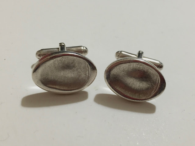 Silver cufflinks with a fingerprint indentation on each one