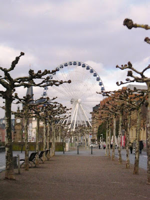Big wheel at the end of a corridor of knobbly trees